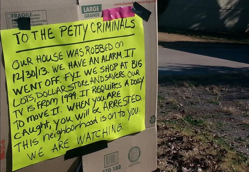 Sign warns burglars neighbors are watching.