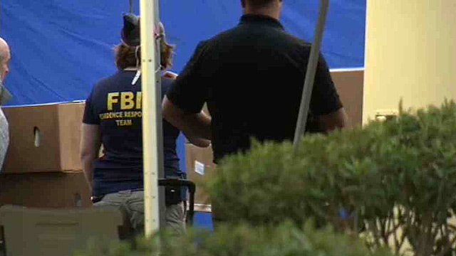 FBI agents watch as cardboard boxes believed to contain body parts are removed from a human tissue bank in Phoenix on Tuesday. (Source: CBS 5 News)