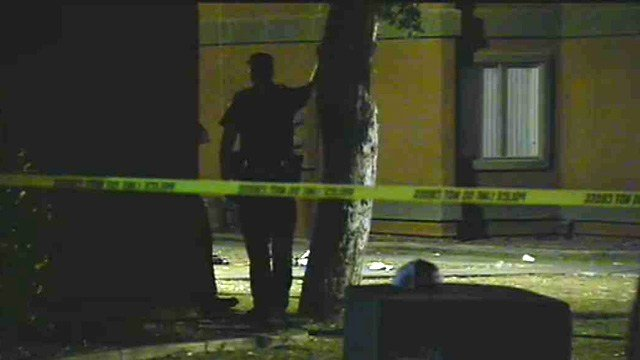 A Phoenix police officer surveys the scene of a shooting at an apartment complex early Thursday morning.