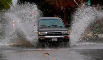 A SUV drives through a flooded portion of a street in Encino, section of Los Angeles Friday, Feb. 28, 2014. (AP Photo/Ringo H.W. Chiu)