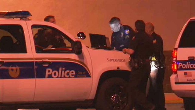 Phoenix police officers investigate an officer-involved shooting at a gun store early Monday morning. (Source: CBS 5 News)