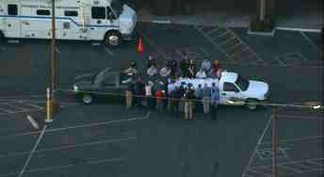 A number of investigators gather for a meeting at the shooting scene. (Source: CBS 5 News)