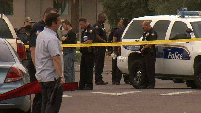 Phoenix police officers gather outside a home where an officer was forced to shoot and kill an erratically behaving man. (Source: CBS 5 News)