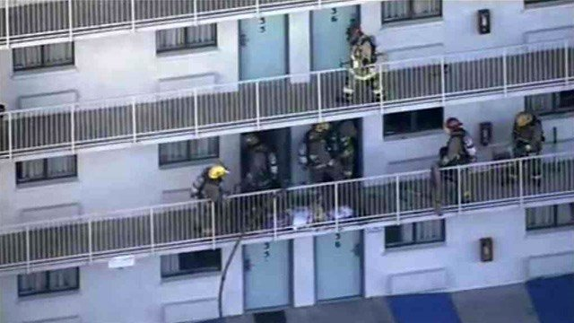 Firefighters work on the second floor of a Motel 6 in Phoenix after a fire broke out in one of the units.