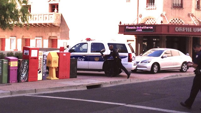 Phoenix police officers run the scene where a suspected carjacker was shot to death Tuesday. (Source: Gib McKay)
