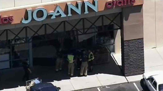 Mesa firefighters look at the front of a Jo-Ann store after a car plowed into the entrance, injuring four people, three seriously.