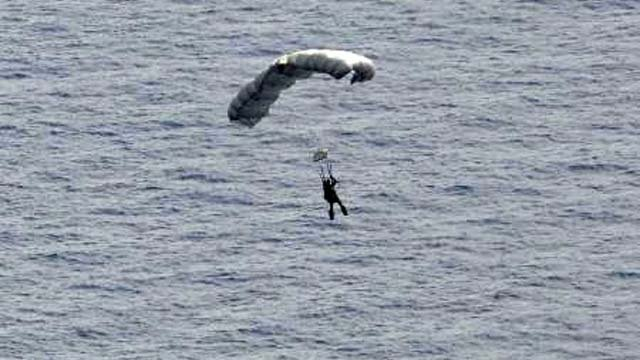 A U.S. Air Force pararescue Airman from the 48th Rescue Squadron parachutes into the Pacific Ocean to aid to two critically injured sailors. (U.S. Air Force photo by Staff Sgt. Adam Grant)