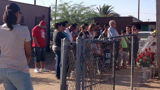 Family and friends of the victim hold a vigil outside his home in Eloy. (Source: Allyson Blair, cbs5az.com)