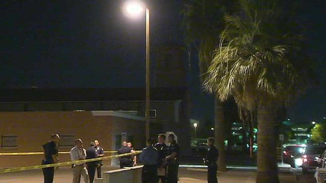 Phoenix police gather near Mother of Mercy Mission Catholic Church where a priest was shot to death and another badly injured Wednesday night. (Source: CBS 5 News)