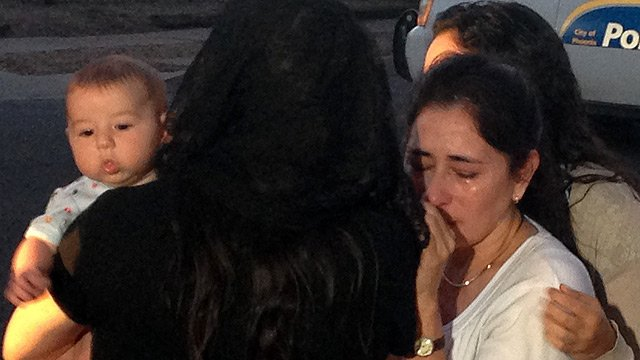 The woman comfort each other as the grief grows over news of the priest's killing. (Source: CBS 5 News)
