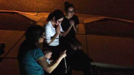 Three women pray the Rosary at Mother of Mercy Mission Catholic Church in Phoenix after a priest was found dead and another badly injured. (Source: CBS 5 News)