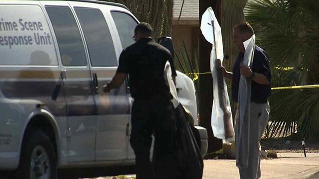 Phoenix police investigators plastic bags of evidence and guns found in a house where two men were killed Tuesday night. (Source: CBS 5 News)