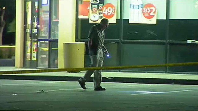 A Phoenix investigator checks the parking lot of a Circle K store in Phoenix, where a man was shot to death. (Source: CBS 5 News)