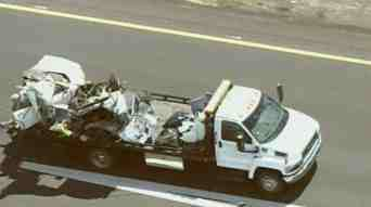 A tow truck carts away one of the mangled vehicles. (Source: CBS 5 News)