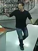 A would-be robber holds up Paradise Valley Boutique on Nov. 21, 2013. (Source: Silent Witness)