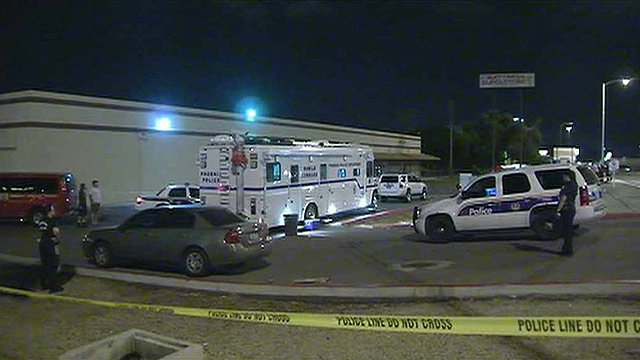 Phoenix police comb the scene for clues after a man's body was found in this parking lot near I-17 and Dunlap Avenue on Thursday night. (Source: CBS 5 News)