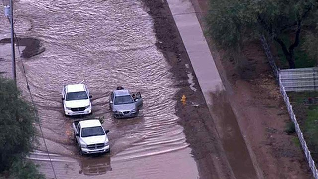 People push a stalled car out of a flooded roadway Tuesday morning after storm surge dropped substantial amounts of rain. (Source: CBS 5 News)