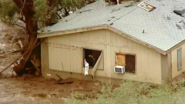 A man waves a white sheet after he became trapped in this house near 46100 N. 43rd Ave. in New River after a raging flood. (Source: CBS 5 News)