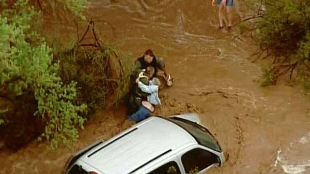 Rescuers free a woman high water trapped her in a van near 153rd Avenue and Dynamite Road. (Source: CBS 5 News)