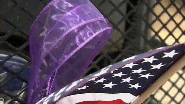 An American flag flanked by the traditional purple ribbon in Yarnell serve as a memorial to the 19 firefighters who died fighting the Yarnell Hill Fire. (Source: CBS 5 News)