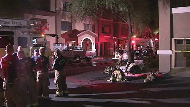 Scottsdale firefighters gather in front of an apartment complex in which a fire started in one of the units. (Source: CBS 5 News)
