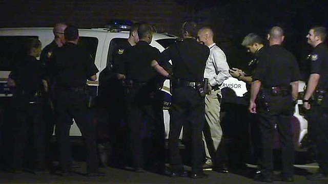 Phoenix police officers gather after a heavily-armed man who fired at officers was shot and killed Monday night. (Source: CBS 5 News)