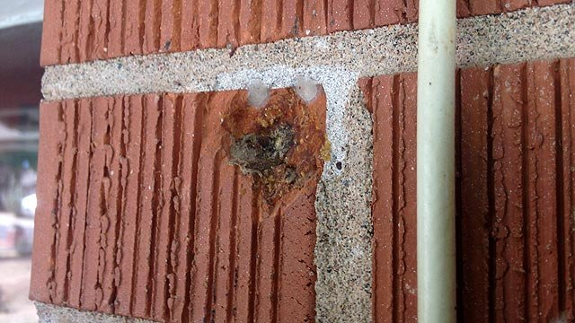 A bullet struck the brick exterior of a home across the street from the suspect's. (Source: CBS 5 News)