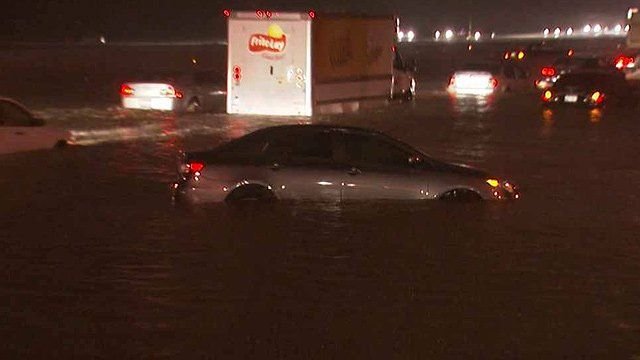 A stalled car floats in the water near 48th Avenue and Interstate 10 after a thunderstorm rolled through the Valley on Monday morning. (Source: CBS 5 News)