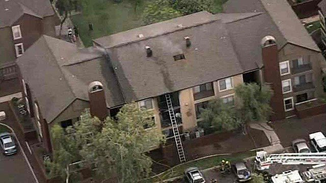 Smoke billows makes it was through a hole in the roof of a three-story apartment building Monday morning. (Source: CBS 5 News)