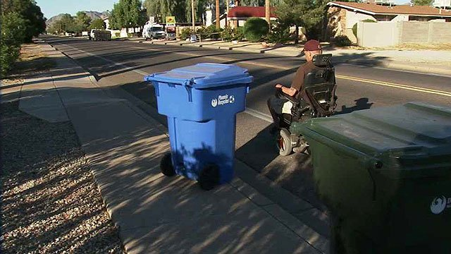 Aaron Edgell is forced to take his motorized wheelchair into the street to get around trash cans improperly placed on a sidewalk in Phoenix. (Source: CBS 5 News)