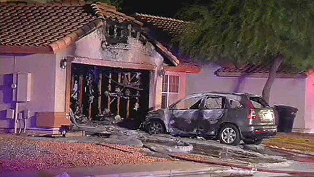 A car that was burned during a garage fire sits in the driveway of this Chandler house Wednesday morning. (Source: CBS 5 News)