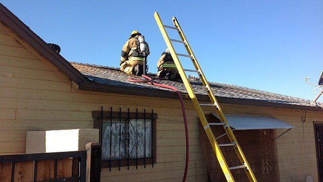 Phoenix firefighters check the roof of a home after an attic fire Thursday morning. (Source: Phoenix Fire Department)