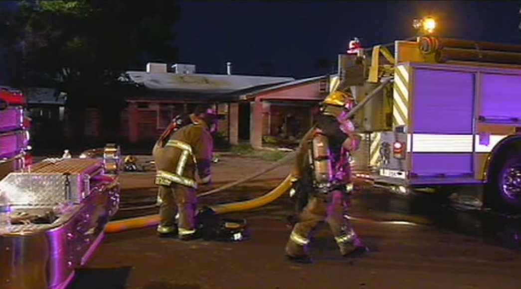 Firefighters clean up after a fire badly damaged this home in Goodyear. (Source: CBS 5 News)