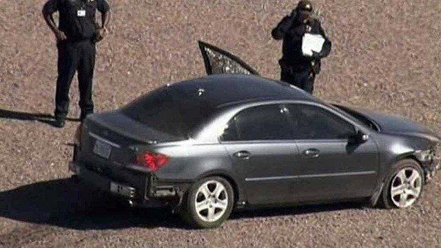 Phoenix police inspect the outside of a sedan in which a man was found dead and with a gunshot wound. (Source: CBS 5 News)