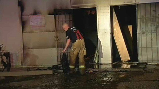 A Phoenix firefighter clears debris from a commercial building fire in Phoenix on Friday morning. (Source: CBS 5 News)