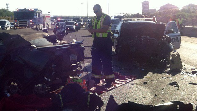 Mesa firefighters check under the wreckage of one of three cars involved in a collision on U.S. Highway 60 in Mesa on Tuesday morning. (Source: Arizona Department of Public Safety)