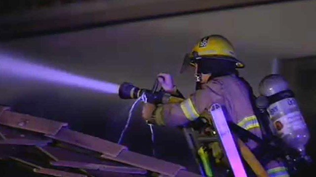 A Peoria firefighter sprays the roof of the garage. (Source: CBS 5 News)