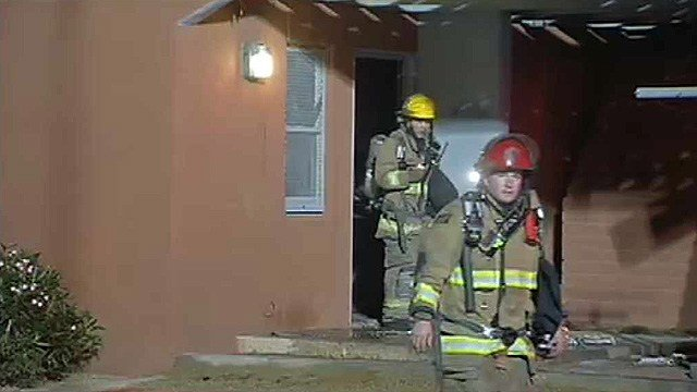 Firefighters leave the ground floor of an apartment badly damaged by fire. A woman inside the apartment was in extremely critical condition after she was found in her bed. (Source: CBS 5 News)