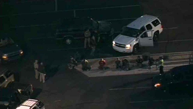 DPS officers hold suspects in a Food City parking lot Tuesday morning. (Source: CBS 5 News)