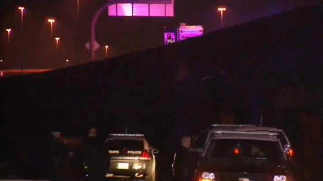 Tempe police vehicles sit near the spot where a man landed after jumping over a freeway wall on the Loop 202 Red Mountain Freeway early Friday morning. (Source: CBS 5 News)