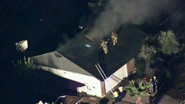 Glendale firefighters attack a Friday morning house fire from the roof. (Source: CBS 5 News)