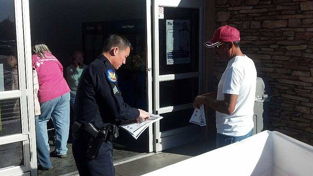A Phoenix police officer hands out flyers warning against random gunfire at a Walmart at 5250 W. Indian School Road on Thursday. (Source: CBS 5 News)
