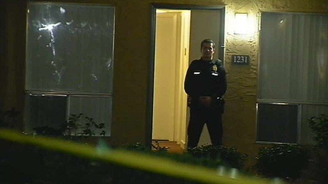 A Phoenix police officer stands in the doorway of an apartment at a complex where a woman was wounded by a bullet Thursday night. (Source: CBS 5 News)