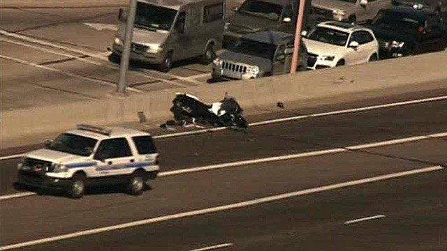 A Scottsdale police cruiser drives past a motorcycle that crashed and closed Loop 101 in Scottsdale on Tuesday morning. (Source: CBS 5 News)