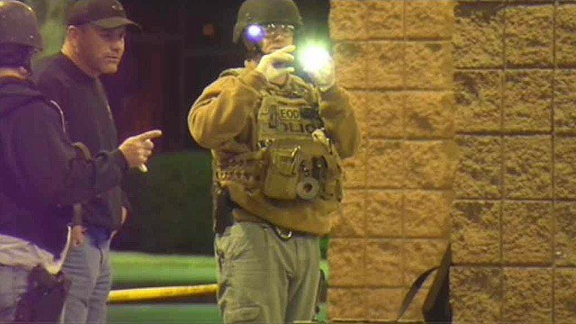 Tempe explosives experts survey the scene of a car fire at a QT station Wednesday night. (Source: CBS 5 News)
