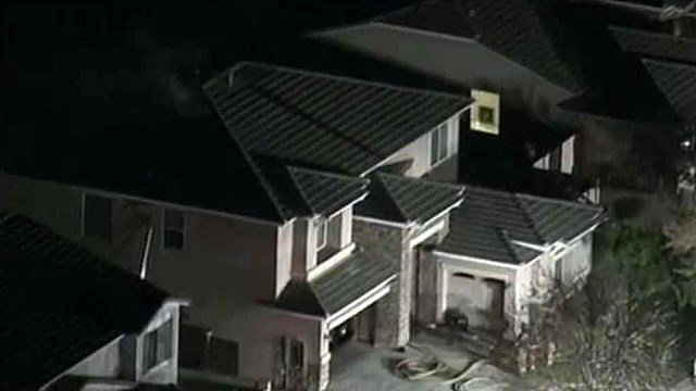 Smoke emanates from the roof of a Gilbert house after a bathroom fan caught fire Thursday morning. (Source: CBS 5 News)