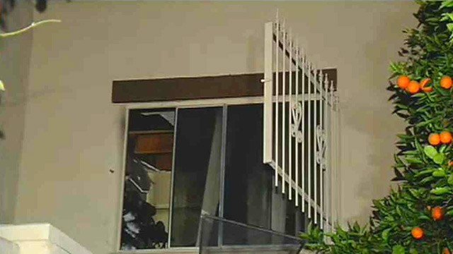 A Scottsdale woman escaped serious injury from a fire in her apartment when she climbed out of this second-story window and was helped to safety by a neighbor. (Source: CBS 5 News)