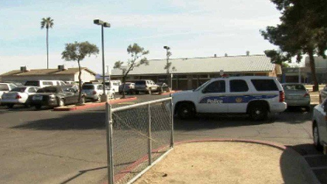 A Phoenix officer patrols the parking lot at Carl Hayden High School on Thursday afternoon after a threatening note was found on the campus Tuesday. (Source: CBS 5 News)
