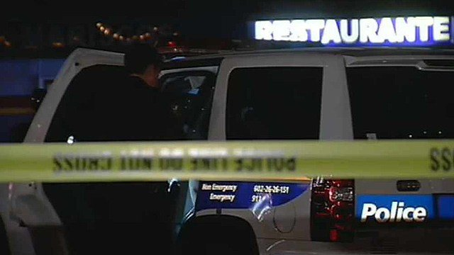 A Phoenix police officer is at the scene of a shooting in which two people, including a bouncer, were shot and wounded at a bar near 32nd and Oak streets early Friday. (Source: CBS 5 News)