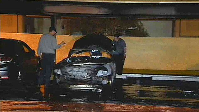 Tempe fire investigators look at one of two vehicles set on fire at an apartment complex early Thursday morning. (Source: CBS 5 News)